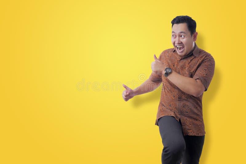 Happy Funny Asian Man Wearing Indonesian Batik Dancing Full of Joy stock photography