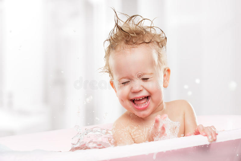 Happy funny baby laughing and bathed in bath. Happy funny baby laughing and bathed in the bath royalty free stock photography