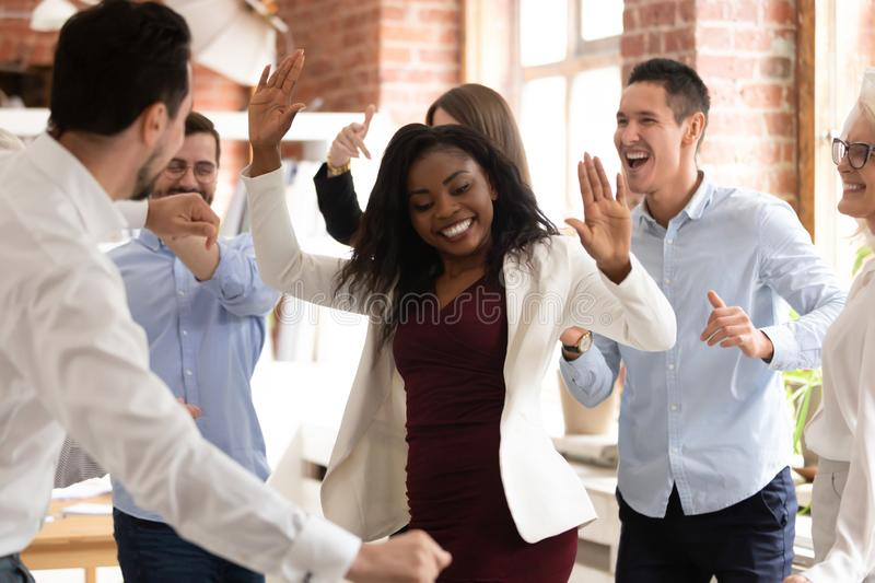 Happy funny black businesswoman with diverse team enjoy victory dance. Happy funny black business women with diverse team coworkers enjoy victory dance concept stock images