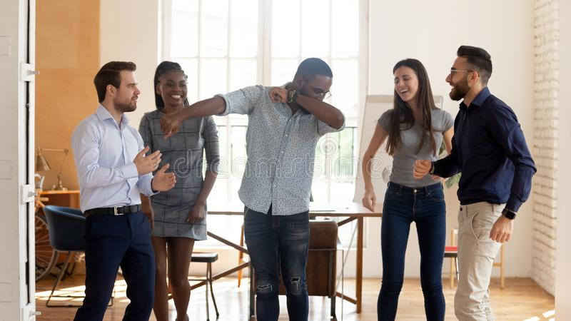 Happy funny black businesswoman with diverse team enjoy victory dance. Happy funny motivated diverse business team people celebrating success win or enjoying royalty free stock photo