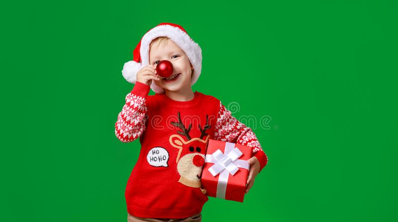 Happy funny child boy in red Christmas reindeer costume with gift on green   background royalty free stock image