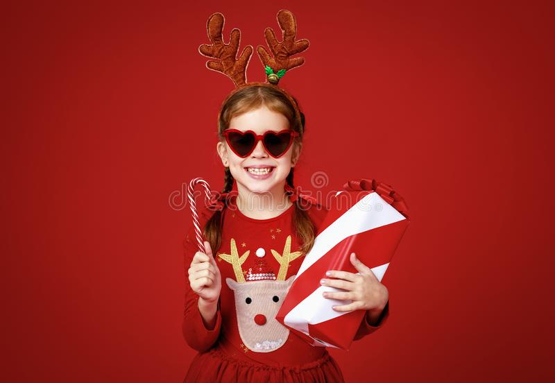 Happy funny child girl in   Christmas reindeer costume with gift, sunglasses and candy on red   background royalty free stock images