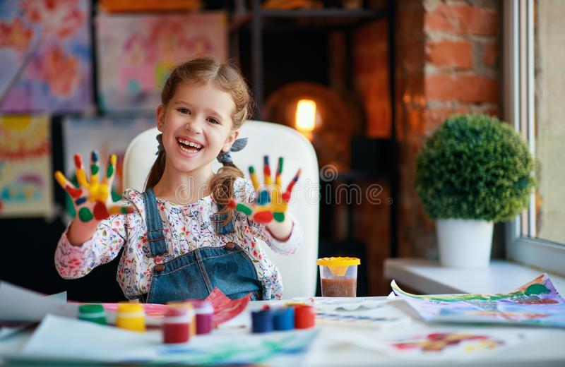 Funny child girl draws laughing shows hands dirty with paint. Happy funny child girl draws laughing shows hands dirty with paint stock image
