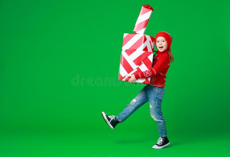 Happy funny child girl in red Christmas hat   with gift on green   background stock photo