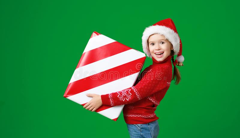 Happy funny child girl in red Christmas hat   with gift on green   background stock photos