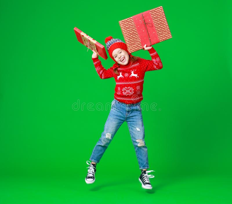 Happy funny child girl in red Christmas hat   with gift jumping on green   background royalty free stock image