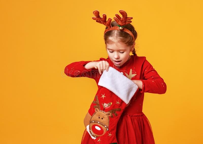 Happy funny child girl in red Christmas reindeer costume with gift surprise sock on yellow   background stock photos