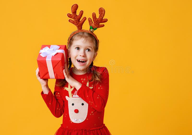 Happy funny child girl in red Christmas reindeer costume with gift on yellow   background royalty free stock photo