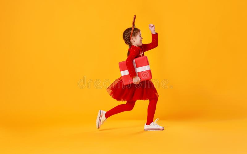 Happy funny child girl in red  running with Christmas gift on yellow background royalty free stock photos