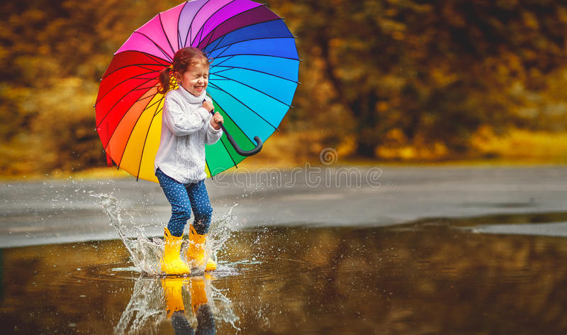 Happy funny child girl with umbrella jumping on puddles in rubb. Happy funny ba child by girl with a multicolored umbrella jumping on puddles in rubber boots and stock images