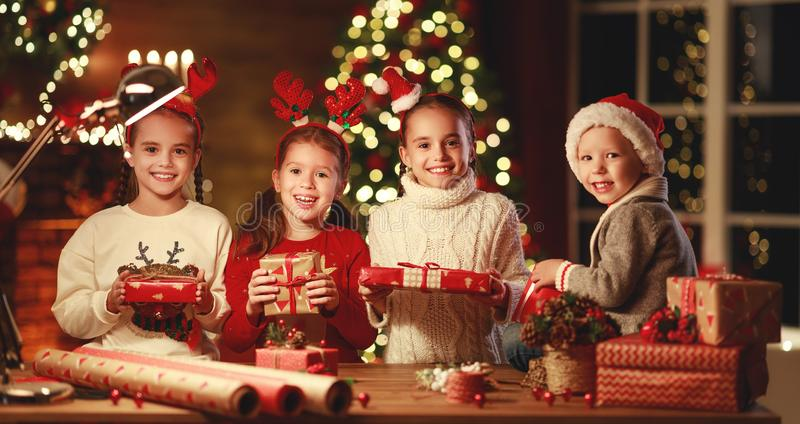 Happy funny children girls pack Christmas gifts at evening in home royalty free stock image
