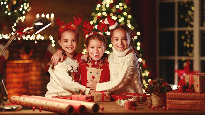 Happy funny children girls pack Christmas gifts at evening in home stock photo