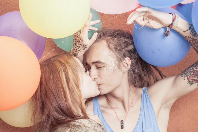 Happy and funny couple kissing at background of color balloons royalty free stock photography