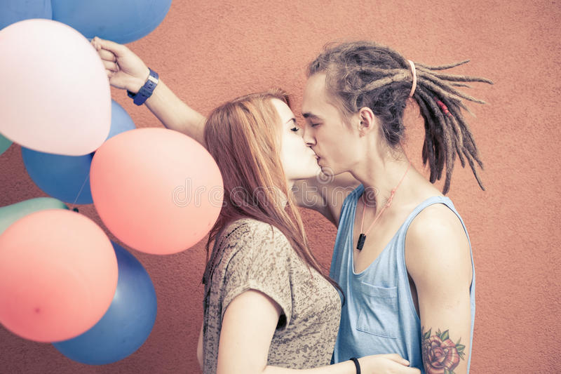 Happy and funny couple kissing at background of color balloons stock photography