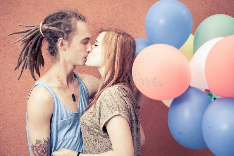 Happy and funny couple kissing at background of color balloons royalty free stock image