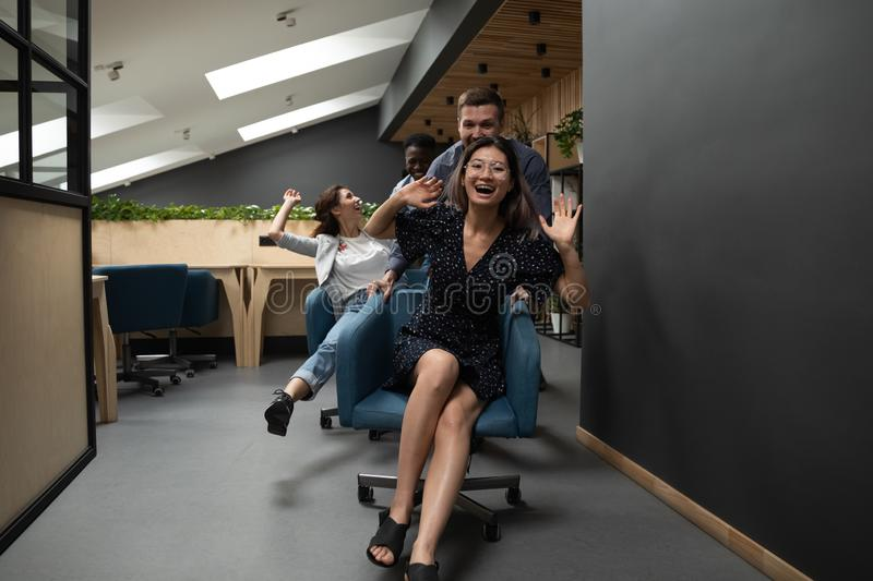 Happy funny diverse coworkers riding on chairs in modern office. Happy funny friendly diverse coworkers having fun racing riding on chairs in modern office stock photos