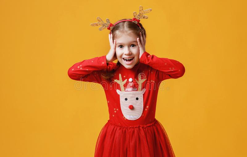 Happy funny emotional child girl in red Christmas reindeer costume  on yellow   background royalty free stock photos