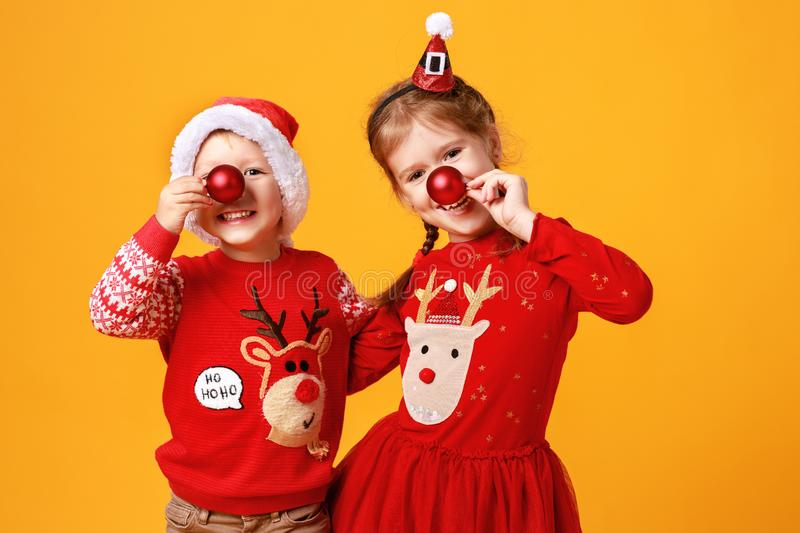 Happy funny emotional children boy and  girl in red Christmas reindeer costume  on yellow   background stock photography