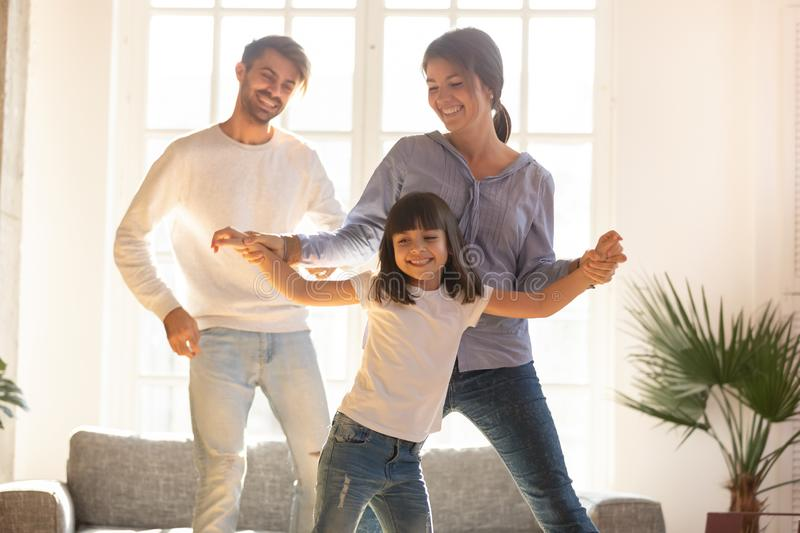 Happy family and child daughter laughing dancing in living room. Happy funny family and cute little child daughter laughing dancing in modern living room, joyful stock image