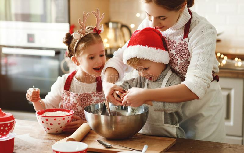 Happy family mother and children bake christmas cookies stock photos