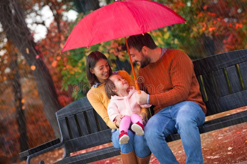 Happy funny family with red umbrella under the autumn shower royalty free stock image