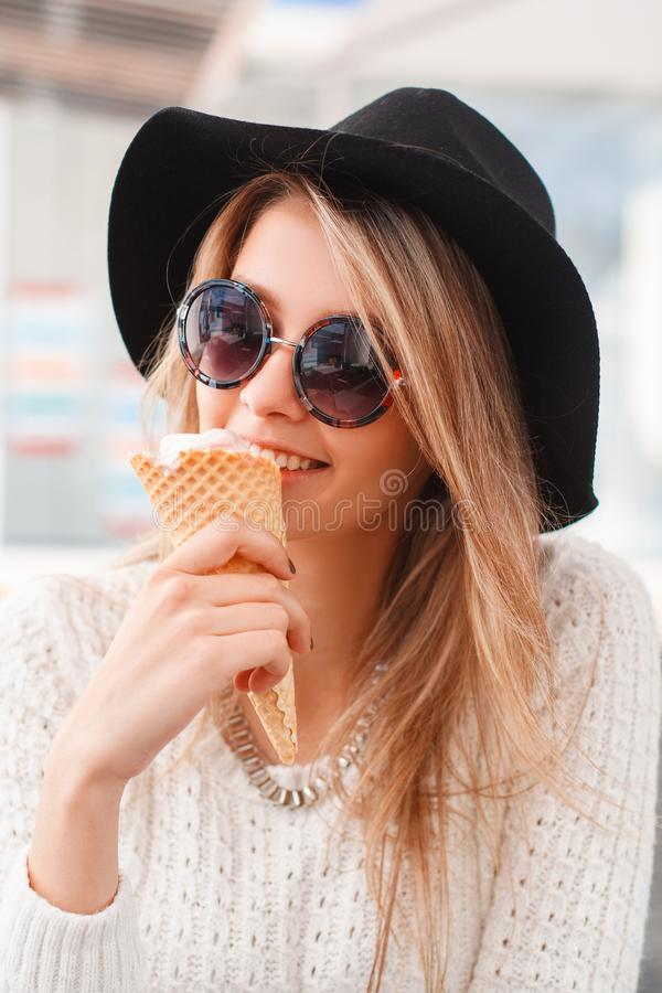 Happy funny hipster young woman in elegant black hat in a knitted sweater sits and eats sweet ice cream in a summer cafe. stock image