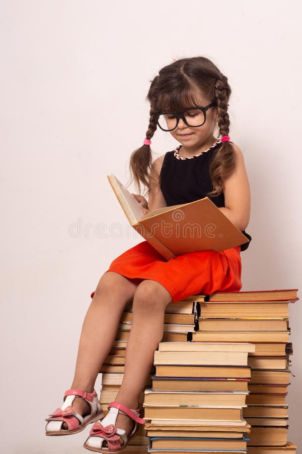 Happy funny kid girl in glasses reading a book in a library. Knowledge, development and education. royalty free stock photography