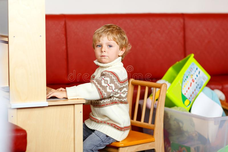 Happy funny little blond child playing with lots of educational toys and cars indoor. Kid boy wearing colorful clothes royalty free stock photos