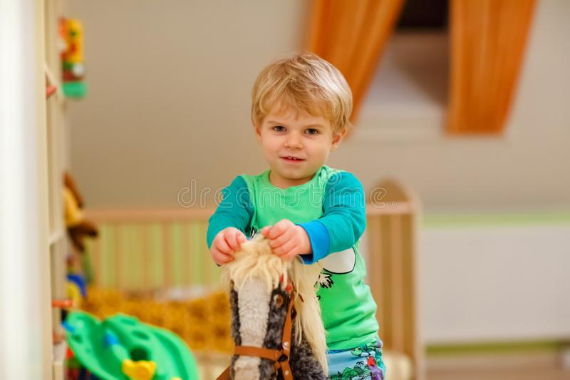 Happy funny little blond child playing and riding on toy horse indoor. Kid boy wearing colorful shirt and having fun at stock images