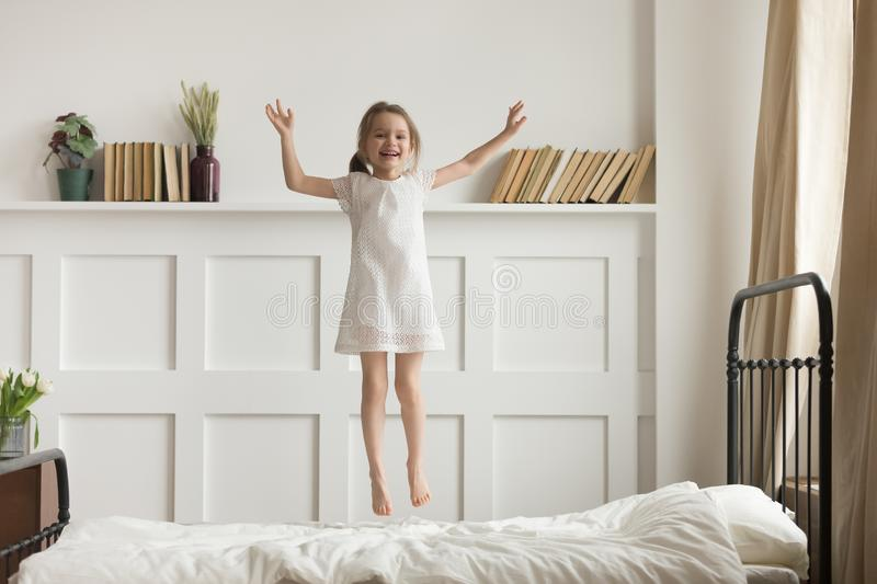 Happy funny child girl jumping on bed alone feeling joy royalty free stock photo