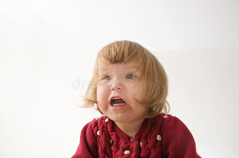 Happy funny little girl emotional playing. cute caucasian blond baby girl with bear and doll royalty free stock photo