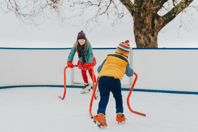 Happy funny little kids practicing with support on skating rink royalty free stock images