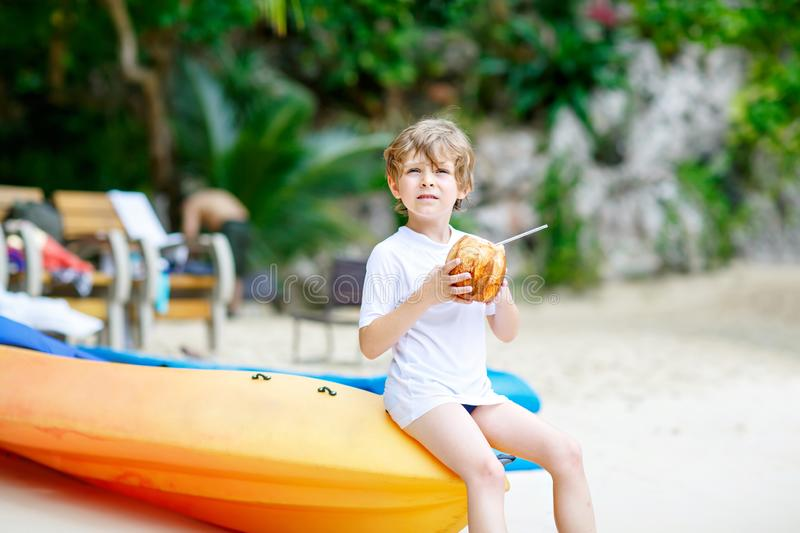 Happy funny little preschool kid boy drinking coconut juice on ocean beach. child playing on family vacations on. Tropical island. summer, happiness, childhood stock photography