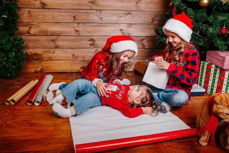 Happy funny little sisters in Santa hats pack gifts near Christmas tree. Happy funny little sisters in Santa hats pack Christmas gifts stock photos