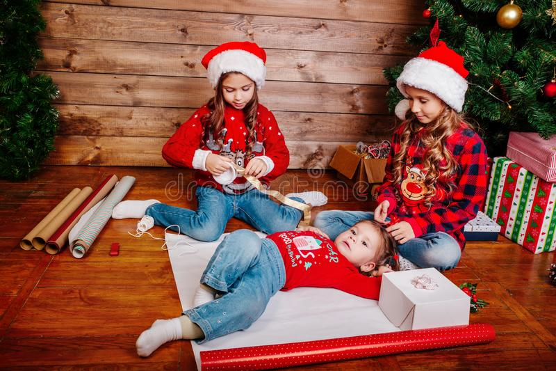 Happy funny little sisters in Santa hats pack gifts near Christmas tree. Happy funny little sisters in Santa hats pack Christmas gifts royalty free stock photography