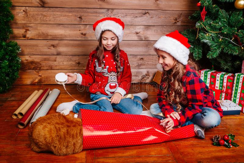 Happy funny little sisters in Santa hats pack gifts near Christmas tree. Happy funny little sisters in Santa hats pack Christmas gifts royalty free stock images