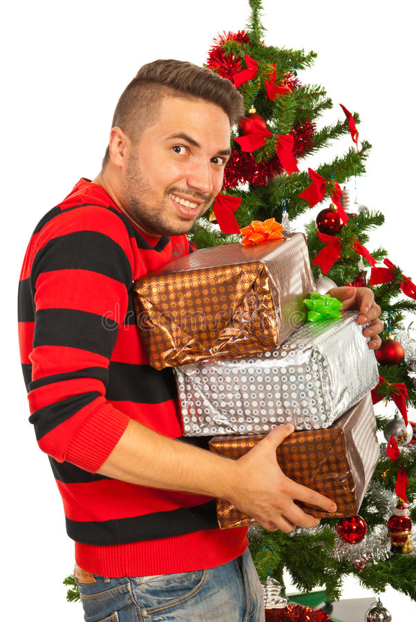 Happy funny man with stack of presents. Funny man with stack of Christmas presents in front of tree want to stole them royalty free stock images