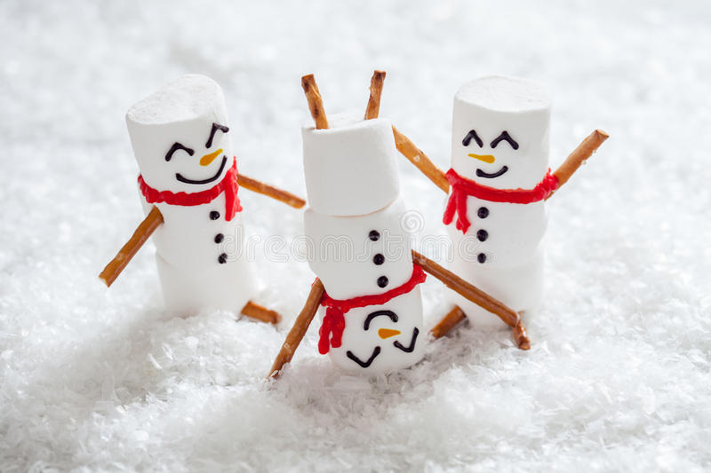 Happy funny marshmallow snowmans on snow. Happy funny marshmallow snowmans are having fun in snow stock photo