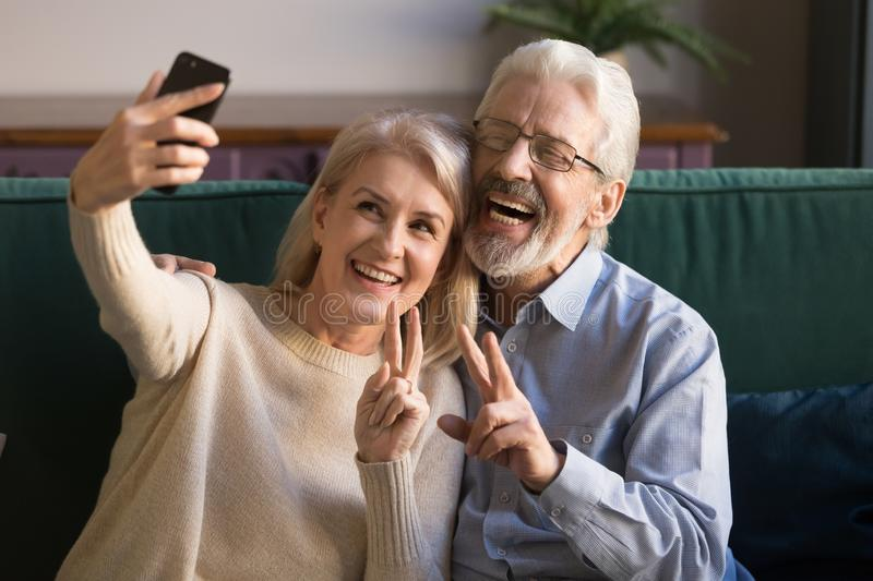 Happy funny mature senior couple taking selfie looking at smartphone stock photos