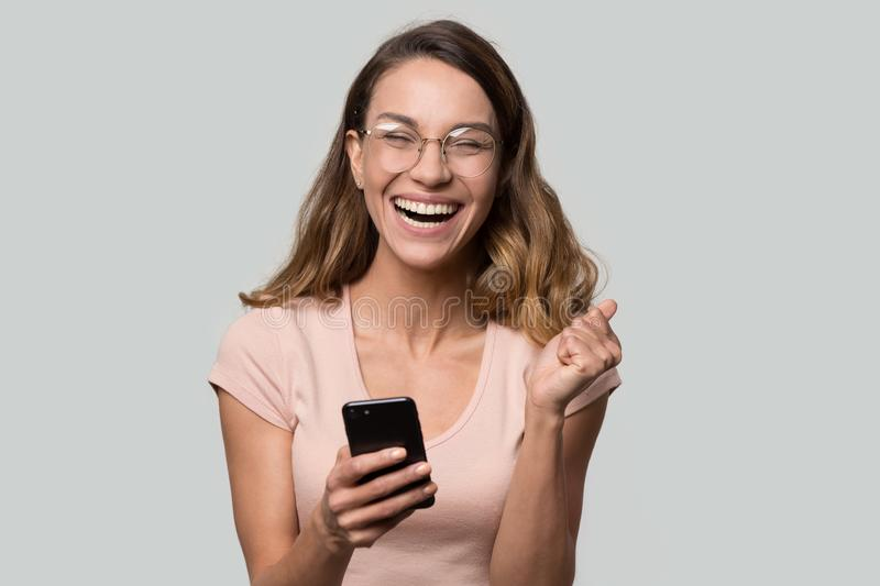 Happy funny millennial woman celebrating mobile win isolated on background royalty free stock photos