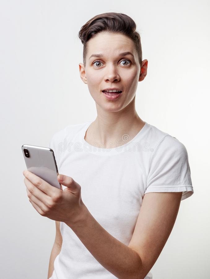 Happy funny millennial woman`s celebrating win or victory, triumph, holding a phone. Cheerful excited girl, laughing, having fun, stock photos