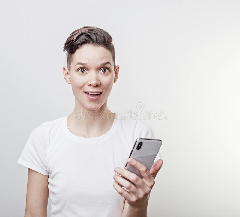 Happy funny millennial woman`s celebrating win or victory, triumph, holding a phone. Cheerful excited girl, laughing, having fun, stock images