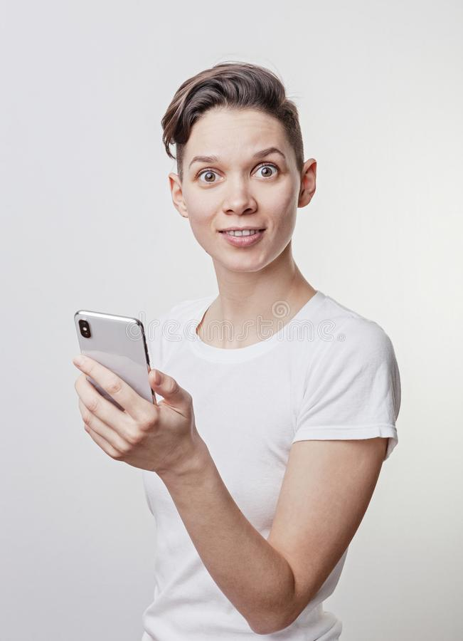 Happy funny millennial woman`s celebrating win or victory, triumph, holding a phone. Cheerful excited girl, laughing, having fun, royalty free stock photos
