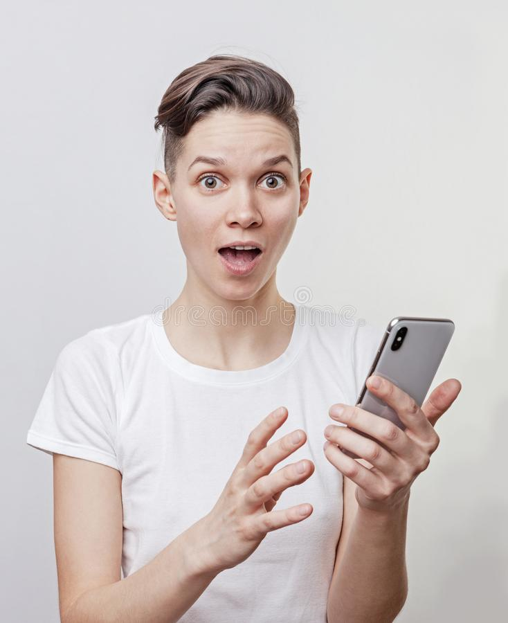 Happy funny millennial woman`s celebrating win or victory, triumph, holding a phone. Cheerful excited girl, laughing, having fun, royalty free stock photo