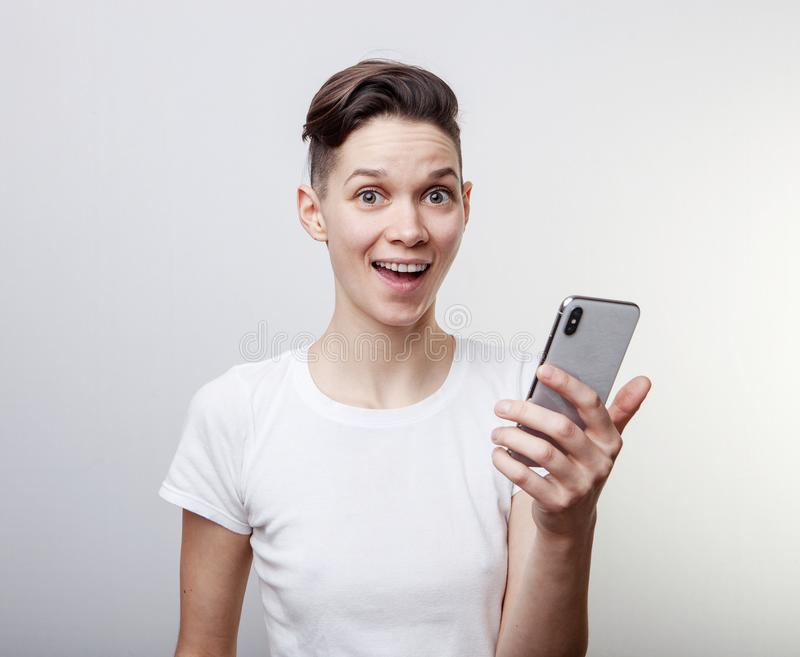 Happy funny millennial woman`s celebrating win or victory, triumph, holding a phone. Cheerful excited girl, laughing, having fun, royalty free stock images