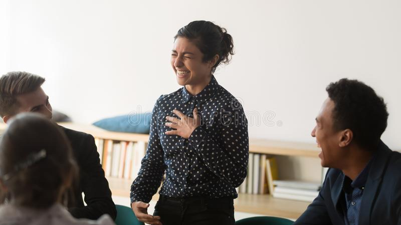 Happy funny indian woman business leader and diverse team laughing. Happy funny shy indian women business leader and diverse team employees people group laughing stock photography
