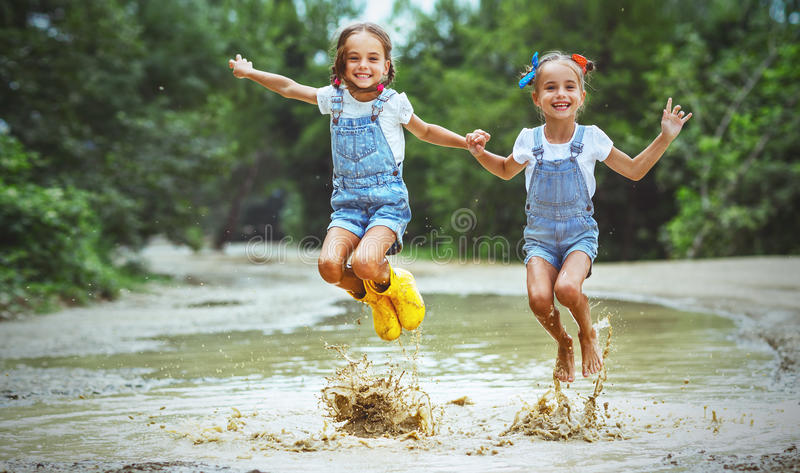 Happy funny sisters twins child girl jumping on puddles in rub royalty free stock images