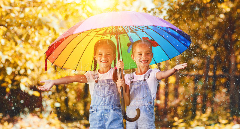 Happy funny sisters twins child girl with umbrella in autumn. Happy funny sisters twins child by girl with a multicolored umbrella laughing in autumn royalty free stock images
