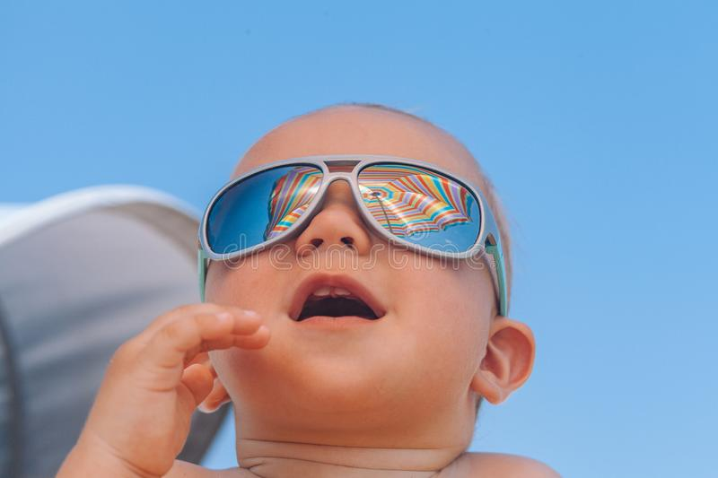 Happy funny smiling cute baby boy with sunglasses. Adorable Happy funny smiling cute baby boy with sunglasses on the beach stock image