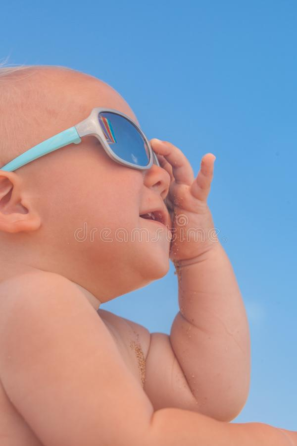 Happy funny smiling cute baby boy with sunglasses. Adorable Happy funny smiling cute baby boy with sunglasses on the beach royalty free stock photography